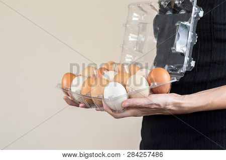 Caucasian Woman With Black Shirt Holding A Plastic Egg Box Full Of Hen Eggs.