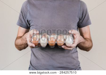 Caucasian Man With Gray Tshirt Holding A Plastic Egg Box Full Of Hen Eggs.