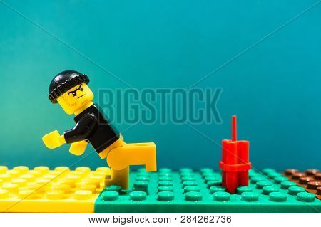 Poznan, Poland - February 13, 2019: Lego Man With Hat Running Away From Dynamite Ready To Explode So