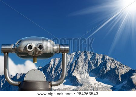 Coin Operated Electronic Binoculars For Tourists On A Blurred Landscape, Mountain Peak With Glacier