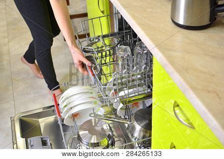 Dishwasher Machine In A Home Kitchen, Loading Process Close Up