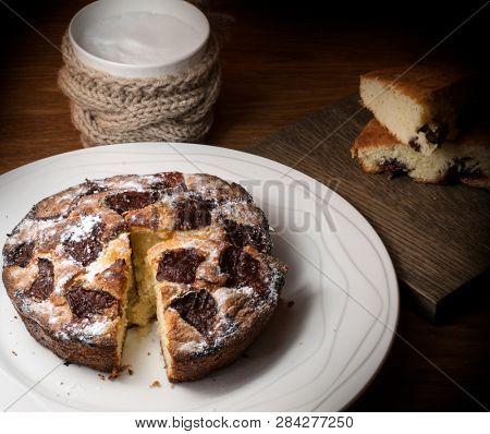 Plum Pie. Rustic plum cake on wooden background