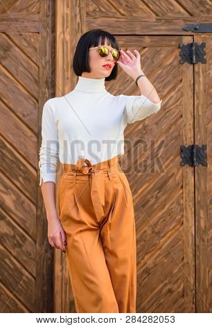Woman Fashionable Brunette Stand Outdoors Wooden Background. Girl With Makeup Posing In Fashionable