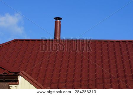 Red Tile Roof And Chimney Against The Blue Sky