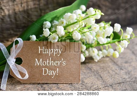 Bouquet Of Lilies Of The Valley With Happy Mothers Day Tag Card On Wooden Background.lily-of-the-val