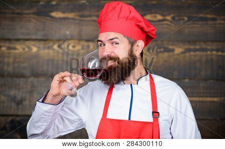 Hipster Wear Hat And Apron Enjoy Aroma Of Drink. Man Master Chef Hold Glass Of Wine. Which Wine Serv