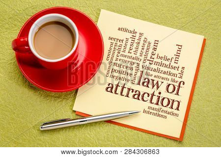 law of attraction word cloud on a paper note with cup of coffee