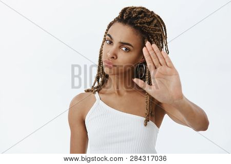 Confident Serious-looking Displeased And Annoyed African American Woman With Dreadlocks Raising Palm
