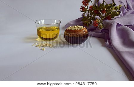 Safflower. Safflower Oil, Seeds In A Container And Scattered On A White Surface And Stems With Flowe