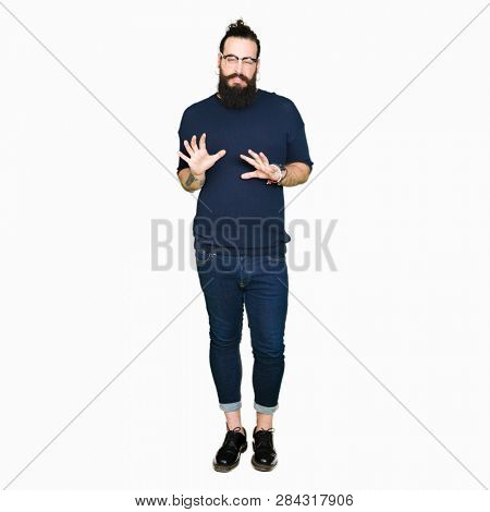 Young hipster man with long hair and beard wearing glasses disgusted expression, displeased and fearful doing disgust face because aversion reaction. With hands raised. Annoying concept.