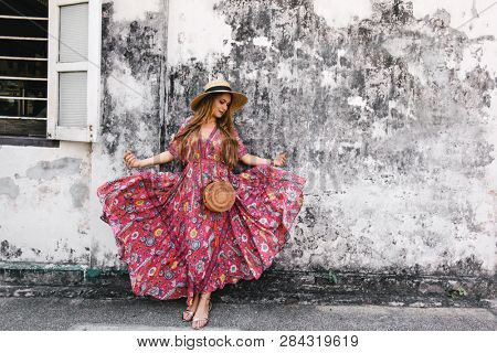 Boho girl in maxi dress and straw hat walking on the Asia city street. Travelling in Phuket Old Town in Thailand.
