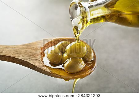 Bottle Of Virgin Olive Oil Pouring To The Spoon Close Up