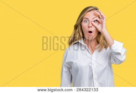 Beautiful young business woman over isolated background doing ok gesture shocked with surprised face, eye looking through fingers. Unbelieving expression.