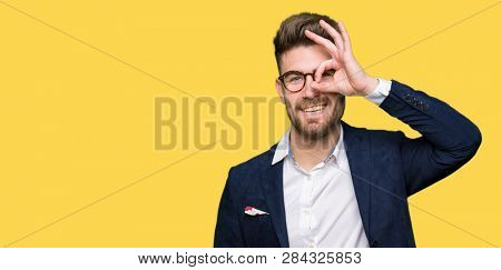 Young handsome business man wearing glasses doing ok gesture with hand smiling, eye looking through fingers with happy face.