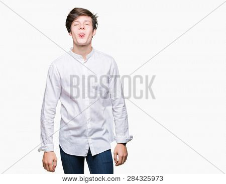 Young handsome business man over isolated background sticking tongue out happy with funny expression. Emotion concept.