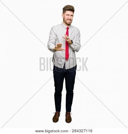 Young handsome business man disgusted expression, displeased and fearful doing disgust face because aversion reaction. With hands raised. Annoying concept.