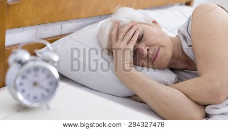Worried Senior Woman Suffering From Insomnia, Having Headache In Bed, Touching Her Forehead, Panoram
