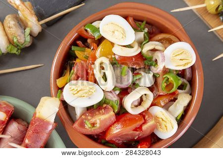 Top View Of Spanish Tapas Snacks With Olives, Squid, Anchovies And Peppers