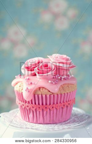 Cupcake with pink flowers on a blue background