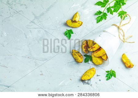 Baked Potato Wedges On Paper With Parsley