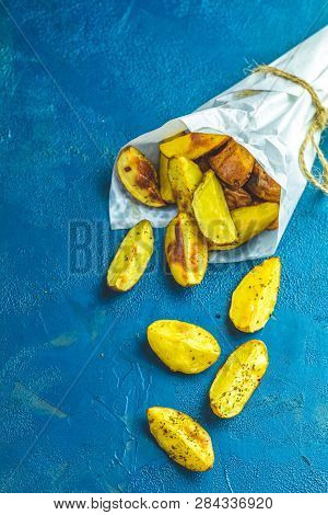 Baked Potato Wedges On Paper With Addition Sea Salt On A Dark Blue Concrete Background