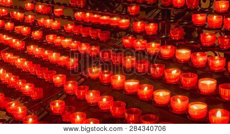 Lots Of Red Easter Candles Burning In Chirch