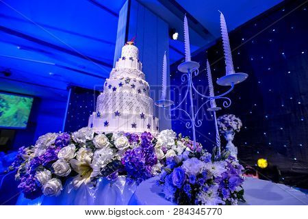 Cake For Wedding Day.wedding Cake With Stage Lighting In Wedding Ceremony.white Cake And Candle For