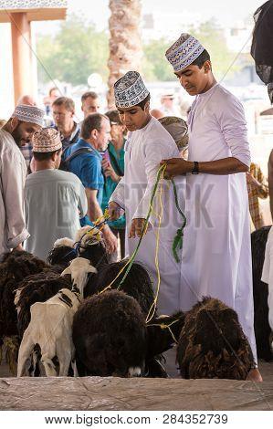 Nizwa, Oman - November 2, 2018: Guys Bring Goats To The Animal Market At Nizwa