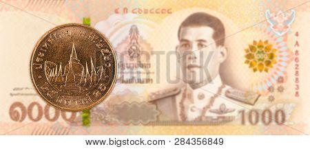 25 Thai Satang Coin Against 1000 New Thai Baht Banknote