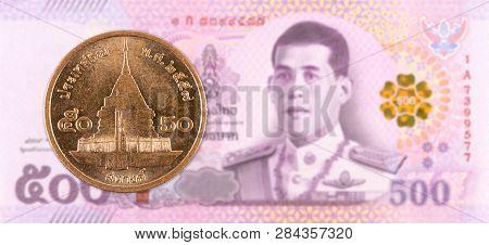 50 Thai Satang Coin Against 500 New Thai Baht Banknote