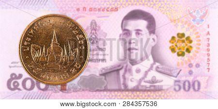 25 Thai Satang Coin Against 500 New Thai Baht Banknote