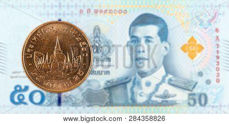 25 Thai Satang Coin Against 50 New Thai Baht Banknote