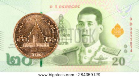 50 Thai Satang Coin Against 20 New Thai Baht Banknote