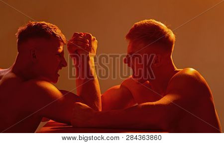The Focus On Strength. Twins Men Competing Till Victory. Twins Competitors Arm Wrestling. Men Compet