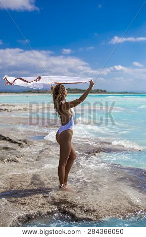Slim young woman at the sea. Girl in white swimsuit with pareo posing against sea poster