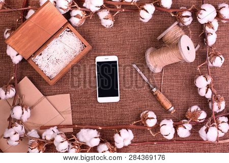 Flower design with fluffy dried cotton bolls gift boxes, white smartphone and jute rope hank over rough brown burlap Top view copy space greeting card poster
