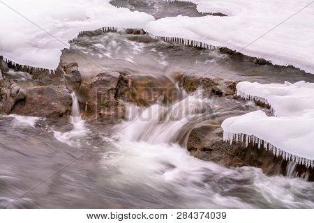 Packed Snow And Ice With Ice-cycles That Look Like Teeth Over Rapidly Flowing Water In River With Ro