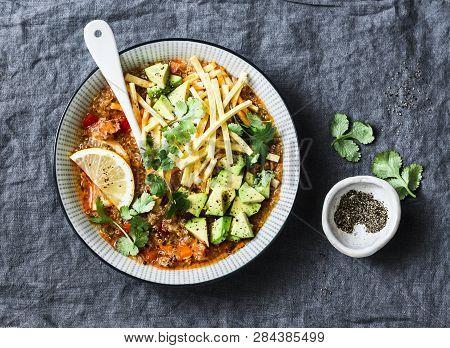 Crock Pot Vegetarian Quinoa Tomato Soup With Corn Tortilla Chips, Avocado And Cilantro On Grey Backg