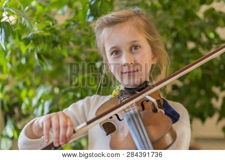 Close Up Of A Child Playing Violin On Isolated Light Background. Portrait Of Girl With String And Pl