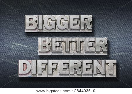 Bigger, Better, Different Words Made From Metallic Letterpress On Dark Jeans Background