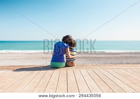 Woman Playing With Her Son On The Beach. The Boy With His Mother Sitting On The Ocean Shore. A Child