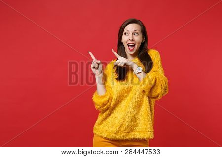 Funny Young Woman In Yellow Fur Sweater Keeping Mouth Open, Looking Pointing Index Fingers Aside Iso