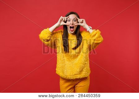 Excited Young Woman In Yellow Fur Sweater Keeping Mouth Wide Open, Stretching Eyelids Isolated On Br