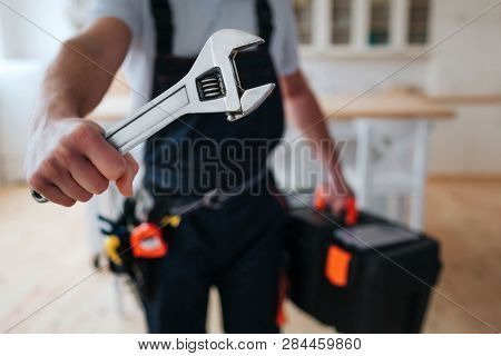 Cut View Of Handyman Holding Tool Box And Wrench In Hands Close To Camera. He Stand In Kitchen. Guy