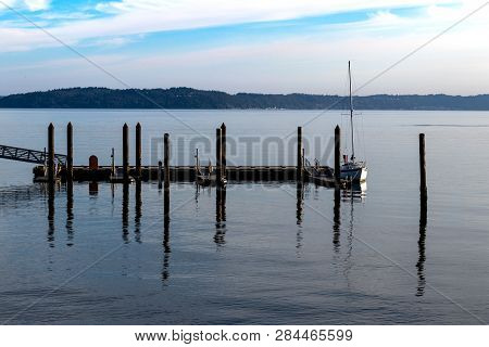 Sailboat Docked At A Pier With Blue Cloudy Sky In Daylight