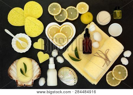 Lemon spa beauty skin care and body care treatment products including  lemons, almond oil, natural soaps, moisturiser, lotion and aromatherapy essential oil. Top view on slate.