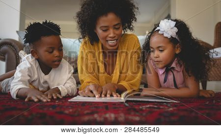 Front view of African American mother with her cute children lying on floor and reading a storybook in a comfortable home