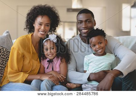 Front view of happy African American family sitting on sofa and looking at in a comfortable home
