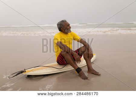 Front view of senior male surfer sitting on the surfboard on beach