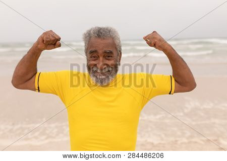 Front view of happy senior man posing and showing his biceps on the beach